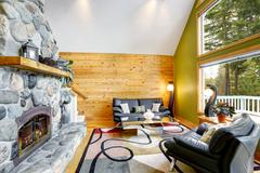 Family room interior with stone wall and wooden wall paneling. There are two  Stock Photos