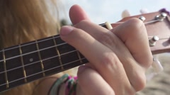 Woman's Hand Clamps Chords on Ukulele Fingerboard. Slow Motion Stock Footage