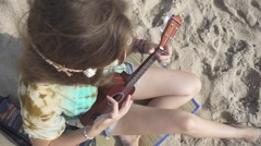 Top View of a Girl Playing Ukulele Sitting on a Beach Sand. Slow Motion Stock Footage