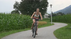 Fit woman cycles along the bike trail Stock Footage
