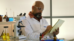 Scientist reading and thinking about notes he has on a pad Stock Footage