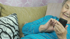 Old woman lying on a beige sofa holds a cellphone Stock Footage