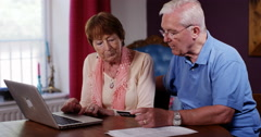 4k, Old couple making online payment from home on their laptop. Stock Footage