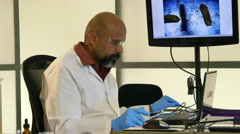 Scientist looking at something on an electronic microscope from a laptop Stock Footage