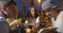 In evening in city of Perea, Greece at the table in cafe sits a young company Stock Footage