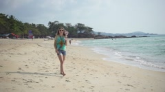 Hippie Girl Walks along the Beach Holding an Ukulele. Slow Motion Stock Footage