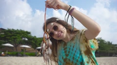 Hippie Girl on the Beach Holds in Her Hand a Dream Catcher. Slow Motion Stock Footage