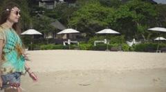 Hippie Girl Walks along the Beach Holding an Ukulele. Slow Motion Stock Footage