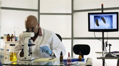 Dolly scientist in lab using a pipette and microscope 4k Stock Footage
