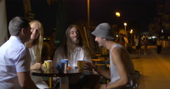 Cheerful group of friends sitting in the evening in the street cafe. All clink Stock Footage