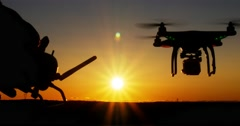 Person operating drone quadcopter aircraft via remote control at sunset Stock Footage