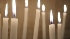 White votive candles burning slowly in the church in act oft Christian prayer Stock Footage