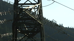 CLOSE UP: Steel sub transmission tower and power lines with forest in background Stock Footage