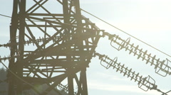 CLOSE UP: Steel transmission tower and power lines behind lush green tree canopy Stock Footage