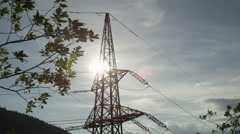 SLOW MOTION: Tall high voltage steel transmission tower behind lush tree branch Stock Footage