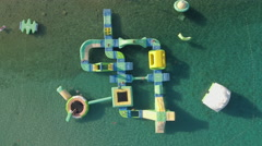 Aerial view of inflated water park on the sea, aquapark Stock Footage