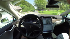 FPV: Tesla electric car self driving through green valley on local road Stock Footage