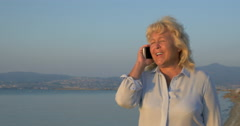 On the sea coast city of Perea, Greece is walking woman and talking on mobile Stock Footage