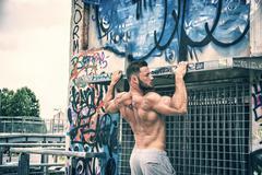 Strong sportsman doing abs exercise outdoor Stock Photos