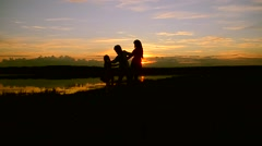 Children with mother whirl on the shore at sunset Stock Footage