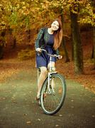 Young girl is riding bike in the park. Stock Photos