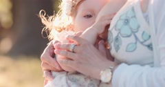 Mother breastfeeding baby daughter in the park. Slow Motion 120 fps 4K Stock Footage