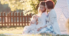 Mother breastfeeding baby in the sunny park, with Grandma near. Slow Motion 4K Stock Footage