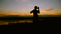 Girl doing selfie phone at sunset in water Stock Footage