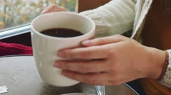 Unrecognizable Young Woman drinking hot Coffee in a Cozy Cafe. 4K. Stock Footage