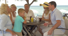 Big family sitting at table on the sea coast in city of Perea, Greece Stock Footage