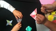 Japanese woman teach a girl how to fold oregami Stock Footage