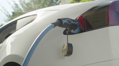 CLOSE UP: Tesla autonomous car charging at home socket on yard on sunny day Stock Footage