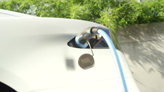 CLOSE UP: Tesla electric car charging on socket at home yard on sunny day Stock Footage