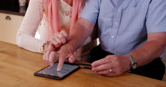4k, Cheerful mature couple e-shopping on their digital touchscreen tablet. Stock Footage