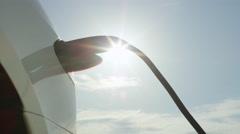 CLOSE UP: Tesla autonomous car recharging batteries under sunny blue sky Stock Footage