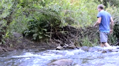 Male hiker crossing rushing stream away from camera Stock Footage
