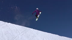 SLOW MOTION: Young pro snowboarder jumping in half pipe snow park Stock Footage