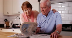 4k, Old couple reading newspaper at home in the morning. Stock Footage