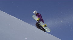SLOW MOTION: Young snowboarder walking uphill carrying his snowboard Stock Footage