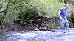 Male hiker crossing rushing stream towards from camera Stock Footage