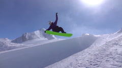 SLOW MOTION: Young pro snowboarder jumping in half pipe in sunny snow park Stock Footage