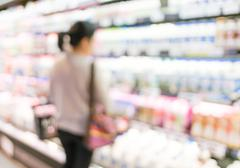 Blur background of woman customer select fresh product on shelf in supermarke Stock Photos