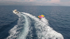 Aerial view of inflatable towable tubes, sofa ride - watersport Stock Footage
