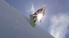 SLOW MOTION: Young pro snowboarder jumping over the sun in half pipe snow park Stock Footage