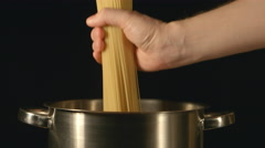 A cook puts down a bunch of spaghetti in a steel pot Stock Footage
