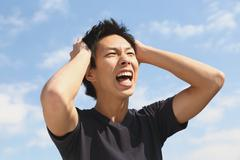 Young Japanese man cheering against blue sky Stock Photos
