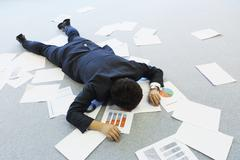 Young Japanese businessman with lots of scattered documents Stock Photos