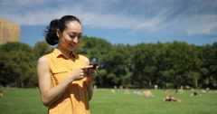 Asian woman in city park texting cell phone Stock Footage