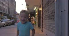 Little boy runs along a busy street of Thessaloniki, Greece Stock Footage