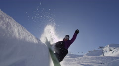 SLOW MOTION: Young pro snowboarder spraying snow in half pipe in sunny snowpark Stock Footage